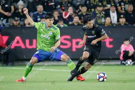 Stock Image of Seattle Sounders defender Kim Kee-hee (20) vies with Los Angeles FC forward Carlos Vela (10) during the first half of the MLS soccer Western Conference final, in Los Angeles