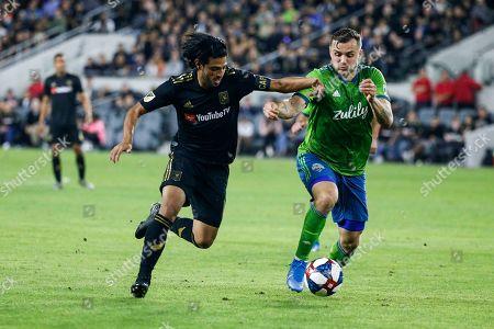 Los Angeles FC forward Carlos Vela, left, vies against Seattle Sounders forward Jordan Morris during the second half of the MLS soccer Western Conference final, in Los Angeles. Seattle Sounders won 3-1