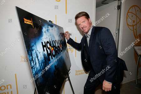 """Jake Busey from """"Stranger Things"""" sign a poster at the membership event, """"Hollywood Horror: Scaring Up an Audience for Television,"""" at the Wolf Theatre at the Saban Media Center at the Television Academy, in Los Angeles"""