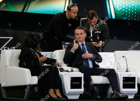 """Steven Mnuchin. Brazilian President Jair Bolsonaro gives a """"thumbs-up"""" sign after adjusting the translation channel during an interview at the Future Investment Initiative forum in Riyadh, Saudi Arabia, . Brazil's president has launched a fiery defense of his far-right government while on a visit to Saudi Arabia, blasting any criticism of his policies on recent fires in the Amazon region"""