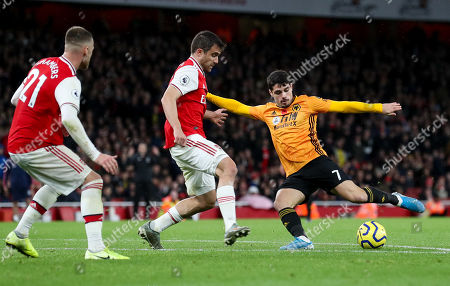 Pedro Neto of Wolves  shoots as Sokratis Papastathopoulos of Arsenal defends with Calum Chambers of Arsenal