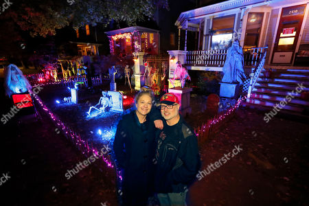 Neighbors Beth LeFauve, left, and Nelson Gonzalez pose for a portrait outside their two Bernard Street homes and the Halloween decorations spanning both properties in Chicago. The good news for kids trick-or-treating this Halloween: They're much more likely to encounter candy than a healthier alternative. Americans this year have a wide variety of plans to celebrate the spooky holiday, from carving pumpkins to watching scary movies. Those are some of the findings of a poll conducted ahead of Halloween by The Associated Press-NORC Center for Public Affairs Research
