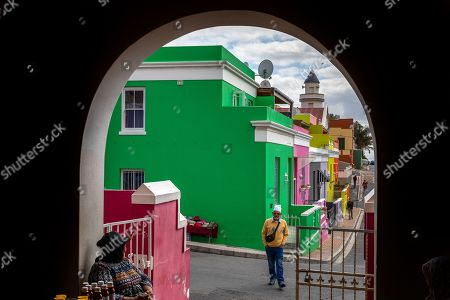A resident of the Bo-Kaap neighborhood crosses a road in Cape Town, South Africa, 30 October 2019. The Bo-Kaap Civic and Ratepayers Association has been awarded a gold certificate at the 2019 Simon van der Stel Awards for its efforts to preserve the heritage of their area. A one billion Rand development on the fringes of the Bo-Kaap was halted by residents in a clash with police in November last year. The Bo-Kaap neighborhood on Signal Hill dates back to the establishment of a Dutch colony on the Cape of Good Hope in the seventeenth century. It is a multi-ethnic and multi-lingual community composed of descendants from South and Southeast Asian nations who had been forcibly relocated to supply skilled labor for the expanding Cape Colony. The Bo-Kaap is recognized globally for its distinctive vernacular architecture and its enduring Muslim culture. The district preserves the largest collection of pre 1850 architecture in South Africa including the countries oldest mosques.  The Bo-Kaap has also been proposed to become South Africa?s first official Lego set. The idea came after Lego fan Wayne Nestadt entered his recreation of the area in the Lego Ideas competition.