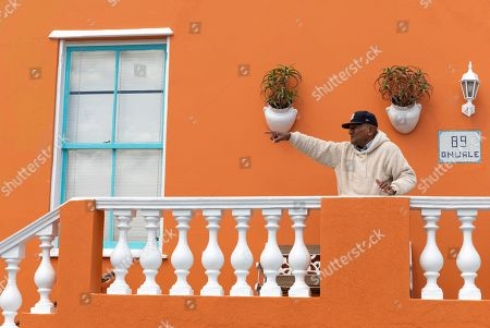 A resident of the Bo-Kaap neighborhood points from his balcony in Cape Town, South Africa, 30 October 2019. The Bo-Kaap Civic and Ratepayers Association has been awarded a gold certificate at the 2019 Simon van der Stel Awards for its efforts to preserve the heritage of their area. A one billion Rand development on the fringes of the Bo-Kaap was halted by residents in a clash with police in November last year. The Bo-Kaap neighborhood on Signal Hill dates back to the establishment of a Dutch colony on the Cape of Good Hope in the seventeenth century. It is a multi-ethnic and multi-lingual community composed of descendants from South and Southeast Asian nations who had been forcibly relocated to supply skilled labor for the expanding Cape Colony. The Bo-Kaap is recognized globally for its distinctive vernacular architecture and its enduring Muslim culture. The district preserves the largest collection of pre 1850 architecture in South Africa including the countries oldest mosques.  The Bo-Kaap has also been proposed to become South Africa?s first official Lego set. The idea came after Lego fan Wayne Nestadt entered his recreation of the area in the Lego Ideas competition.