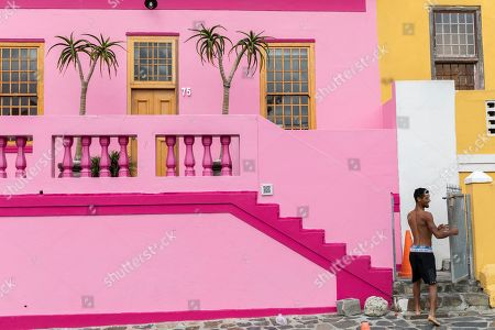 A resident of the Bo-Kaap neighborhood enters his home in Cape Town, South Africa, 30 October 2019. The Bo-Kaap Civic and Ratepayers Association has been awarded a gold certificate at the 2019 Simon van der Stel Awards for its efforts to preserve the heritage of their area. A one billion Rand development on the fringes of the Bo-Kaap was halted by residents in a clash with police in November last year. The Bo-Kaap neighborhood on Signal Hill dates back to the establishment of a Dutch colony on the Cape of Good Hope in the seventeenth century. It is a multi-ethnic and multi-lingual community composed of descendants from South and Southeast Asian nations who had been forcibly relocated to supply skilled labor for the expanding Cape Colony. The Bo-Kaap is recognized globally for its distinctive vernacular architecture and its enduring Muslim culture. The district preserves the largest collection of pre 1850 architecture in South Africa including the countries oldest mosques.  The Bo-Kaap has also been proposed to become South Africa?s first official Lego set. The idea came after Lego fan Wayne Nestadt entered his recreation of the area in the Lego Ideas competition.
