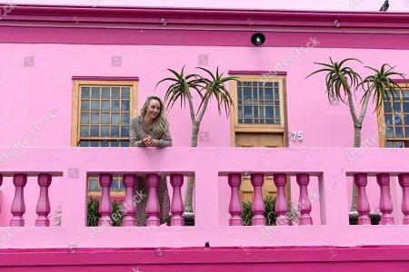 A tourist looks out from a balcony of a home in the Bo-Kaap neighborhood in Cape Town, South Africa, 30 October 2019. The Bo-Kaap Civic and Ratepayers Association has been awarded a gold certificate at the 2019 Simon van der Stel Awards for its efforts to preserve the heritage of their area. A one billion Rand development on the fringes of the Bo-Kaap was halted by residents in a clash with police in November last year. The Bo-Kaap neighborhood on Signal Hill dates back to the establishment of a Dutch colony on the Cape of Good Hope in the seventeenth century. It is a multi-ethnic and multi-lingual community composed of descendants from South and Southeast Asian nations who had been forcibly relocated to supply skilled labor for the expanding Cape Colony. The Bo-Kaap is recognized globally for its distinctive vernacular architecture and its enduring Muslim culture. The district preserves the largest collection of pre 1850 architecture in South Africa including the countries oldest mosques.  The Bo-Kaap has also been proposed to become South Africa?s first official Lego set. The idea came after Lego fan Wayne Nestadt entered his recreation of the area in the Lego Ideas competition.