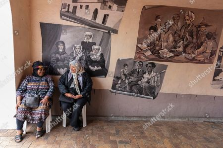 Stock Picture of Residents of the Bo-Kaap neighborhood sit and talk in front of paintings depicting the history of the area in Cape Town, South Africa, 30 October 2019. The Bo-Kaap Civic and Ratepayers Association has been awarded a gold certificate at the 2019 Simon van der Stel Awards for its efforts to preserve the heritage of their area. A one billion Rand development on the fringes of the Bo-Kaap was halted by residents in a clash with police in November last year. The Bo-Kaap neighborhood on Signal Hill dates back to the establishment of a Dutch colony on the Cape of Good Hope in the seventeenth century. It is a multi-ethnic and multi-lingual community composed of descendants from South and Southeast Asian nations who had been forcibly relocated to supply skilled labor for the expanding Cape Colony. The Bo-Kaap is recognized globally for its distinctive vernacular architecture and its enduring Muslim culture. The district preserves the largest collection of pre 1850 architecture in South Africa including the countries oldest mosques.  The Bo-Kaap has also been proposed to become South Africa?s first official Lego set. The idea came after Lego fan Wayne Nestadt entered his recreation of the area in the Lego Ideas competition.