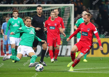 Bremen's Michael Lang (L) in action against Heidenheim's Marc Schnatterer (R) during the German DFB Cup second round soccer match between SV Werder Bremen and FC Heidenheim in Bremen, northern Germany, 30 October 2019.