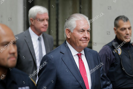 Former Exxon CEO and ex-Secretary of State Rex Tillerson, second from right, leaves a courthouse in New York,. As Exxon faced the prospect of new climate regulations, the energy giant's leaders sought a full understanding of how they would affect the bottom line, Tillerson told a court Wednesday in a securities fraud lawsuit brought by the New York attorney general's office