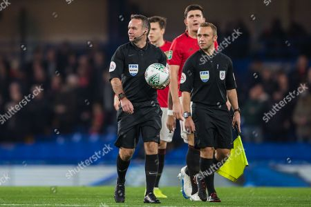 Paul Tierney (Referee) Harry Maguire (Capt) (Man United) and Harry Leonard (Assistant Referee) coming on to the pitch during the EFL Cup match between Chelsea and Manchester United at Stamford Bridge, London