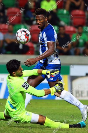 Stock Photo of Maritimo's goalkeeper Amir Abedzadeh (L) in action against FC Porto's Ze Luis (R) during the Portuguese First League soccer match between Maritimo and FC Porto at Barreiros Stadium in Funchal, Portugal, 30 October 2019.