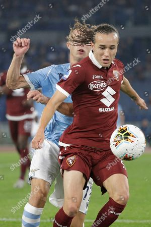 Stock Photo of Lazio's Adam Marusic, left, and Torino's Diego Laxalt vie for the ball during the Italian Serie A soccer match between Lazio and Torino at Rome's Olympic stadium