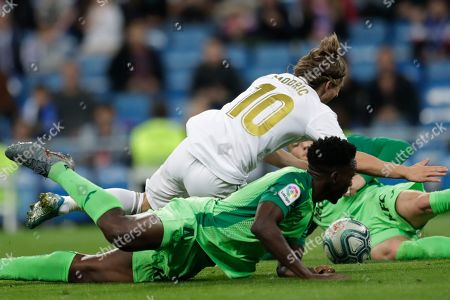 Real Madrid's Luka Modric, top, is fouled by Leganes' Kenneth Omeruo to give away a penalty kick during a Spanish La Liga soccer match between Real Madrid and Leganes at the Santiago Bernabeu stadium in Madrid, Spain