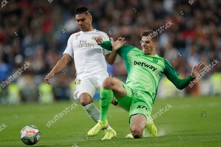 Real Madrid's Casemiro, left, is challenged by Leganes' Christian Rivera during a Spanish La Liga soccer match between Real Madrid and Leganes at the Santiago Bernabeu stadium in Madrid, Spain