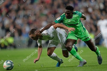 Real Madrid's Eden Hazard, left, falls in front of Leganes' Kenneth Omeruo during a Spanish La Liga soccer match between Real Madrid and Leganes at the Santiago Bernabeu stadium in Madrid, Spain
