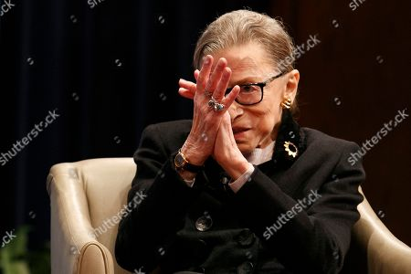 Stock Photo of Supreme Court Justice Ruth Bader Ginsberg applauds at the conclusion of Georgetown Law's second annual Ruth Bader Ginsburg Lecture, with Ginsburg, former President Bill Clinton, and former Secretary of State Hillary Clinton, in Washington