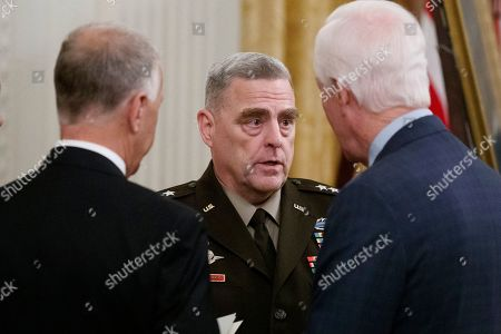 Stock Photo of Sen. Thom Tillis, R-N.C., left, Joint Chiefs Chairman Gen. Mike Milley, and Sen. John Cornyn, R-Texas, talk before for a Medal of Honor Ceremony for U.S. Army Master Sgt. Matthew Williams, currently assigned to the 3rd Special Forces Group, in the East Room of the White House, in Washington