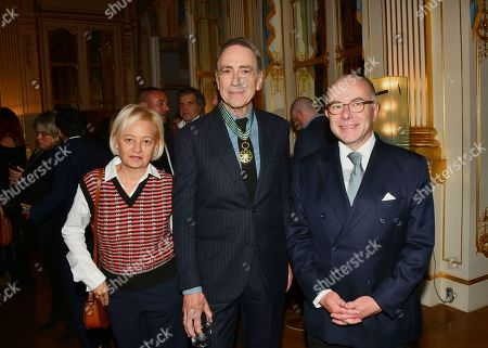 Stock Image of Bernard Cazeneuve and his wife Veronique Beau with Alain Chamfort at the ceremony presenting insignia to members of the Order of Arts and Letters.