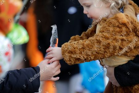 A child dressed as a lion cub reaches for a toothbrush, along with a small piece of candy, being handed out at a dentist's office at a trick-or-treat Halloween event in a business district, in Seattle. Halloween is Thursday, Oct. 31