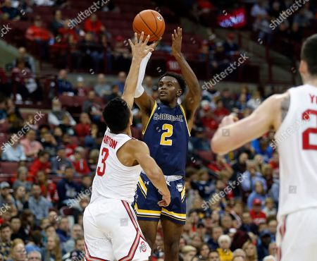 Cedarville guard Branden Maughmer, center, goes up for a shot between Ohio State guard D.J. Carton, left, and forward Kyle Young during the first half of an NCAA college basketball exhibition game in Columbus, Ohio