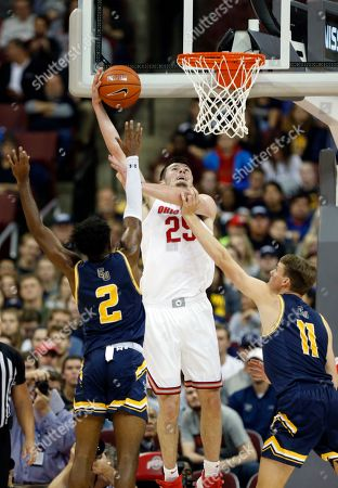 Ohio State forward Kyle Young, center, goes up for a shot between Cedarville guard Branden Maughmer, left, and forward Jacob Drees during the first half of an NCAA college basketball exhibition game in Columbus, Ohio
