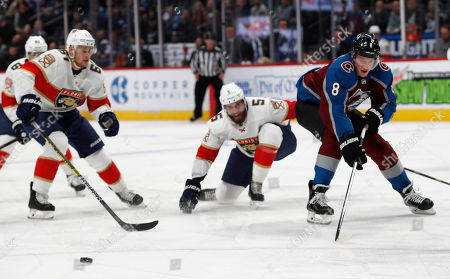 Stock Picture of R m. Colorado Avalanche defenseman Cale Makar, right, loses control of the puck as he drives past Florida Panthers defensemen Aaron Ekblad, center, and Riley Stillman during the first period of an NHL hockey game, in Denver
