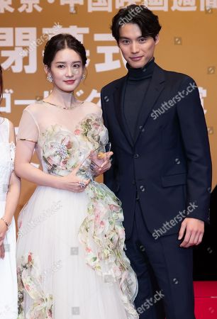 Li Qin holds the Gold Crane Award next to Souta Fukushi at the China Film Week Closing Ceremony during the Tokyo Film Festival
