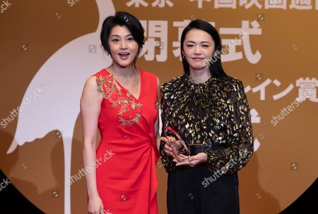 Yao Chen holds the Gold Crane Award while actress Norika Fujiwara pose next to her at the China Film Week Closing Ceremony during the Tokyo Film Festival