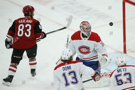 Montreal Canadiens goaltender Carey Price (31) watches the puck float past him on a shot by Arizona Coyotes right wing Conor Garland (83), as Canadiens center Max Domi (13 and defenseman Victor Mete (53) follow the puck during the third period of an NHL hockey game, in Glendale, Ariz. The Canadiens defeated the Coyotes 4-1