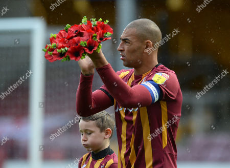 James Vaughan of Bradford City walks on to the pitch with a poppy wreath
