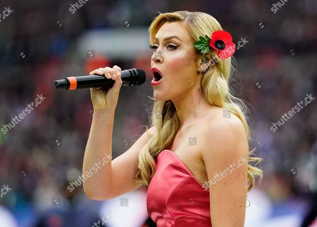 Camilla Kerslake sings the national anthem on the field before kick-off.