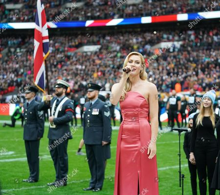 Camilla Kerslake sings the national anthem on the field before kick-off
