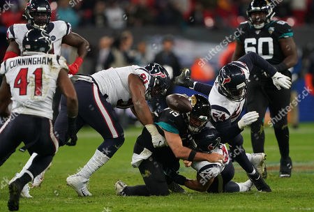 Stock Picture of Jacksonville Jaguars quarterback Gardner Minshew  (15) is tackled by Houston Texans linebacker Dylan Cole  (51), Houston Texans linebacker Jacob Martin  (54) and Houston Texans defensive end Carlos Watkins  (91) and drops the ball