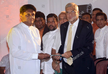 Sajith Premadasa, Ranil Wickremesinghe. Sri Lanka's governing party presidential candidate Sajith Premadasa, left, hands over a copy of his election platform to prime minister Ranil Wickremesinghe in Kandy, Sri Lanka, Thursday, Oct.31, 2019. The voting is scheduled to be held on Nov. 16