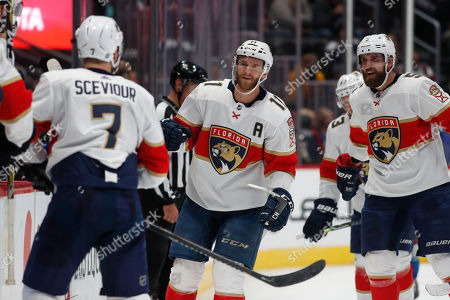 R m. From left, Florida Panthers center Colton Sceviour (7), Florida Panthers center Jonathan Huberdeau (11) and Florida Panthers defenseman Aaron Ekblad (5) celebrate after Huberdeau's goal in the third period of an NHL hockey game against the Colorado Avalanche, in Denver. The Panthers won 4-3 in overtime