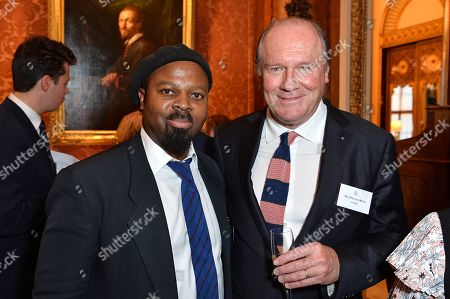 Stock Image of Poet Ben Okri and Author William Boyd during a reception for winners of the Queen's Commonwealth essay competition 2019 at Buckingham Palace