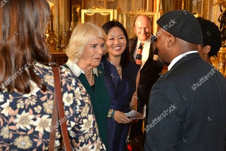 Stock Picture of Camilla Duchess of Cornwall meets with Author Evie Wyld and Poet Ben Okri during a reception for winners of the Queen's Commonwealth essay competition 2019 at Buckingham Palace