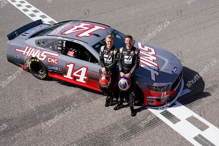 Haas drivers Kevin Magnussen, of Denmark, and Romain Grosjean, of France, pose for a photo by a NASCAR Cup Series car owned by Stewart-Haas Racing at the Formula One U.S. Grand Prix auto race at the Circuit of the Americas, in Austin, Texas