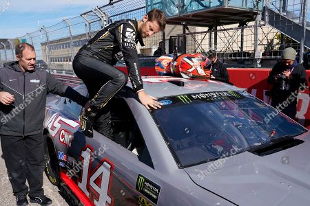 Haas driver Romain Grosjean, of France, climbs into a NASCAR Cup Series car owned by Stewart-Haas Racing at the Formula One U.S. Grand Prix auto race at the Circuit of the Americas, in Austin, Texas