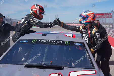 Haas drivers Kevin Magnussen, of Denmark, and Romain Grosjean, right, of France, shake hands after driving a NASCAR Cup Series car owned by Stewart-Haas Racing at the Formula One U.S. Grand Prix auto race at the Circuit of the Americas, in Austin, Texas