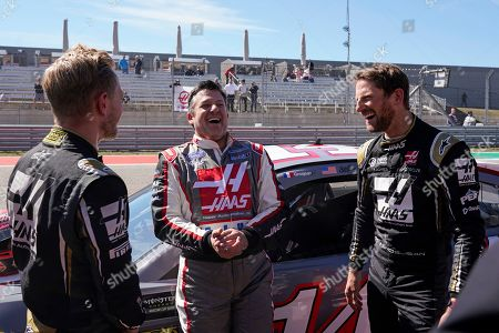 Tony Stewart laughs with Haas driver Kevin Magnussen, of Denmark, and Haas driver Romain Grosjean, of France, at the Formula One U.S. Grand Prix auto race at the Circuit of the Americas, in Austin, Texas