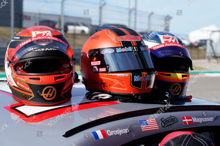 The helmets of Haas driver Kevin Magnussen, of Denmark, Tony Stewart and Haas driver Romain Grosjean, of France, are seen on the top of a NASCAR Cup Series car owned by Stewart-Haas Racing at the Formula One U.S. Grand Prix auto race at the Circuit of the Americas, in Austin, Texas