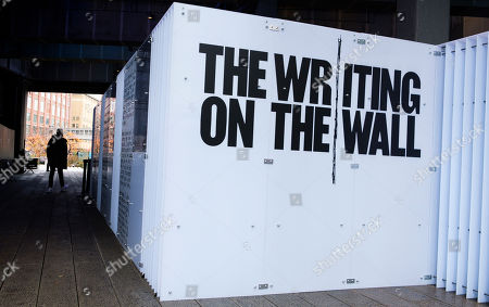 A person walks past the temporary art installation 'The Writing on the Wall', a traveling installation made up of essays, poems, letters, drawings and notes by people in prison around the world, in the Highline park in New York, New York, USA, 31 October 2019. The installation, which is in place from 31 October until 10 November 2019, is a collaboration between artist Hank Willis Thomas and Dr. Baz Dreisinger,  the founder of the Prison-to-College Pipeline program at John Jay College of Criminal Justice.