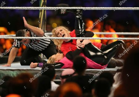 """Saudi fans watch World Wrestling Entertainment """"WWE"""" stars Lacey Evans, at top, takes down Natalya Neidhart as they play the first-ever women's wrestling match in Saudi at King Fahd International Stadium in Riyadh, Saudi Arabia"""
