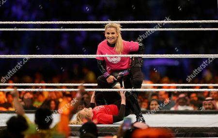 """Saudi fans watch World Wrestling Entertainment """"WWE"""" stars Natalya Neidhart, at top, takes down Lacey Evans as they play the first-ever women's wrestling match in Saudi at King Fahd International Stadium in Riyadh, Saudi Arabia"""