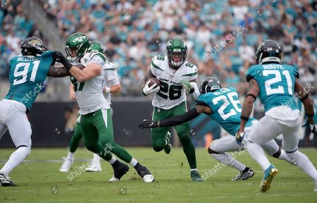 """New York Jets running back Le'Veon Bell (26) rushes for yardage in front of Jacksonville Jaguars defensive back Jarrod Wilson (26), defensive end Yannick Ngakoue (91) and cornerback A.J. Bouye (21) during the first half of an NFL football game in Jacksonville, Fla. Bell didn't like how little he was used in the 29-15 loss at Jacksonville, and Bell needed to make sure Jets coach Adam Gase knew what he was feeling. """"I was a little frustrated,"""" Bell said Thursday. """"I'm always frustrated at a loss, but this was a little different because I wasn't involved and we lost."""" Bell carried the ball eight times for 23 yards and had three catches for 12 yards"""