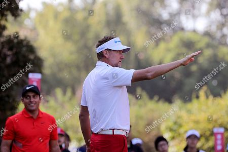 Ian Poulter of England cautions a spectator to put away a mobile phone before Francesco Molinari of Italy at left tees off during the HSBC Champions golf tournament held at the Sheshan International Golf Club in Shanghai on
