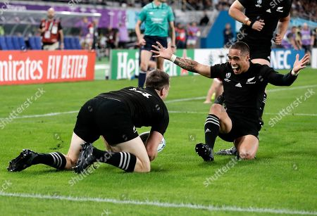New Zealand's Ben Smith, left, is congratulated by teammate Aaron Smith after scoring a try during the Rugby World Cup bronze final game at Tokyo Stadium between New Zealand and Wales in Tokyo, Japan