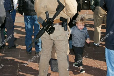 Stock Image of Logan West, Nathaniel West. Logan West, left, and his son Nathaniel West, right, age three, of Cleveland, Okla., attend a rally at the state Capitol to mark the start of a new law that allows most adults in Oklahoma to carry a firearm in public without a background check or training, in Oklahoma City