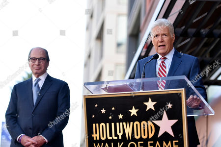 """Harry Friedman, Alex Trebek. Harry Friedman, left, executive producer of """"Jeopardy!"""" and """"Wheel of Fortune,"""" listens as """"Jeopardy!"""" host Alex Trebek speaks at a ceremony honoring Friedman with a star on the Hollywood Walk of Fame, in Los Angeles"""